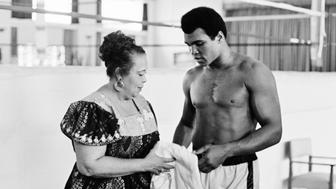 In this photo taken on October 27, 1974 US boxing heavyweight champion Muhammad Ali (born Cassius Clay) stands with her mother Odessa Grady Clay during a training session three days before the heavy weight world championship in Kinshasa. TOn October 30, 1974 Muhammad Ali knocked out George Foreman in a clash of titans known as the 'Rumble in the Jungle', watched by 60 000 people in the stadium in Kinshasa and millions elsewhere. AFP PHOTO        (Photo credit should read STR/AFP/Getty Images)