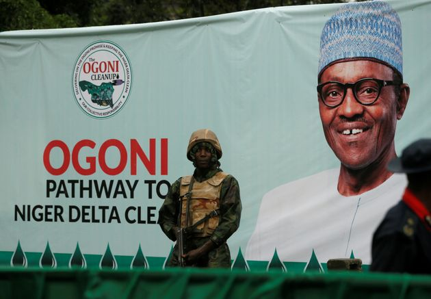 A soldier stands guard in front of a banner with a picture of Nigeria's President Muhammadu Buhari in...