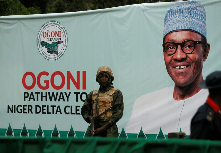 A soldier stands guard in front of a banner with a picture of Nigeria's President Muhammadu Buhari in Gokana during the launc