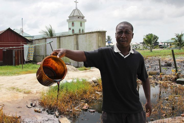 A man shows a bucket of crude oil spilled after a Shell pipeline leaked in the Oloma community of Nigeria's Delta region
