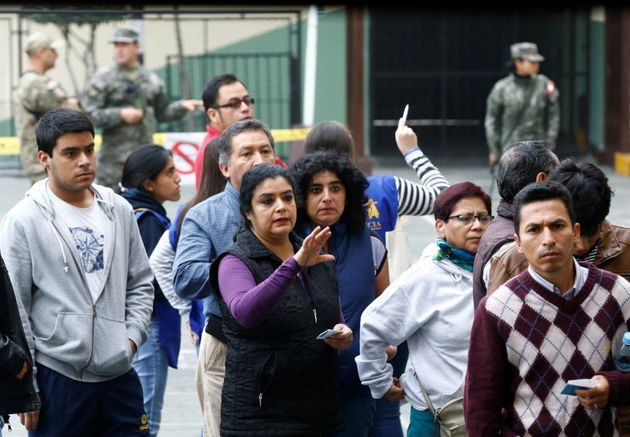 People stand in line to cast their votes in Peru's presidential election at a voting station in Lima,...
