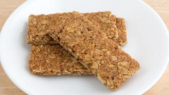 Several cinnamon flavored sesame and pumpkin seed granola bars on a white plate atop a wood table top.