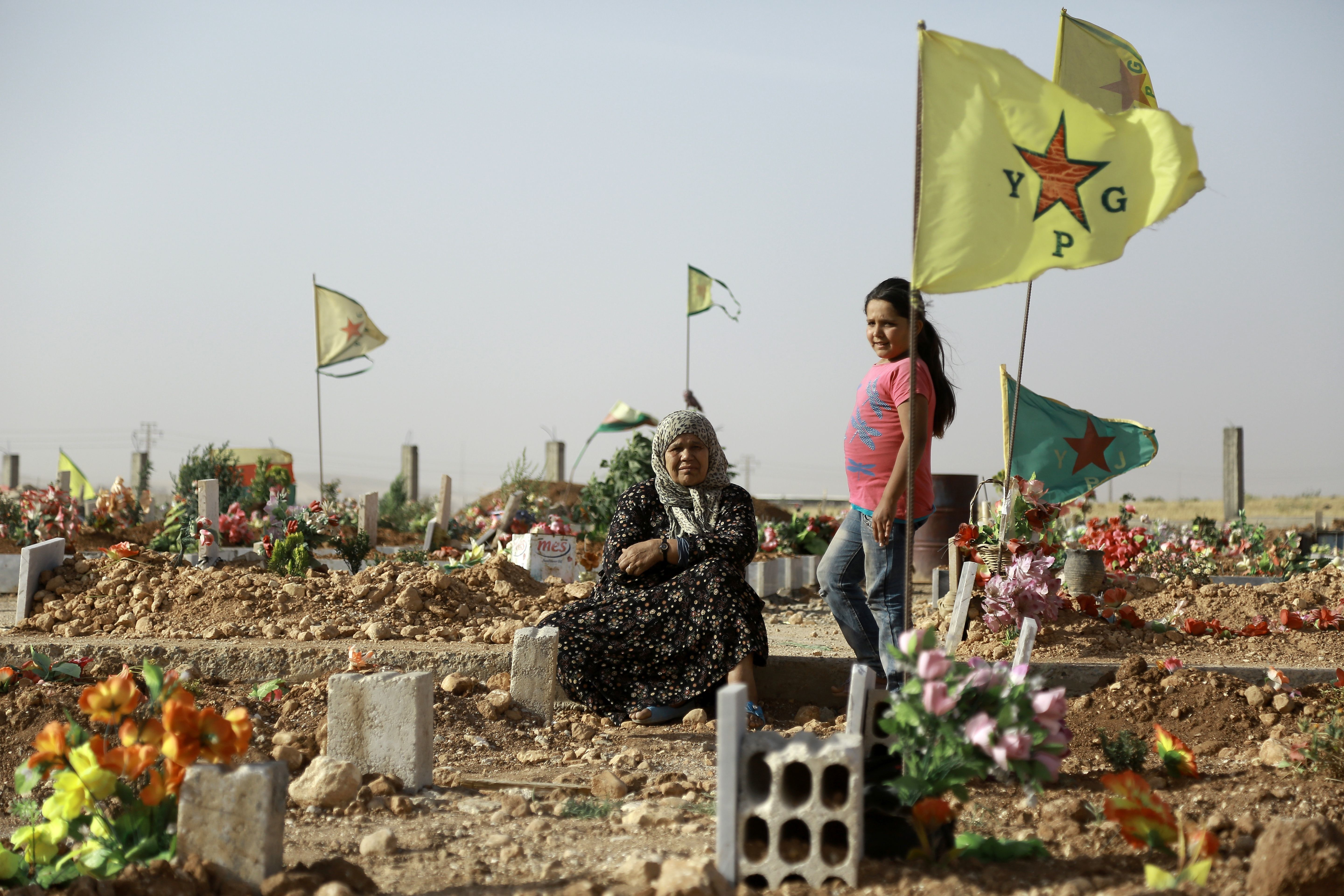 A Syrian Kurdish woman sits next to the grave of a relative during the funeral of fighters, who died during an assault launched by Arab and Kurdish forces against Islamic State (IS) group fighters in the town of Manbij, in the Syrian Kurdish town of Kobane on June 4, 2016.  Arab and Kurdish fighters backed by Washington have launched an assault on the strategic Manbij pocket further up the Euphrates on the Turkish border, regarded as a key entry point for foreign jihadists. The Syrian Democratic Forces's offensive against the Manbij pocket is aimed at seizing the last stretch of border still under IS control and denying the jihadists any opportunity to smuggle in recruits and funds. / AFP / Delil Souleiman        (Photo credit should read DELIL SOULEIMAN/AFP/Getty Images)