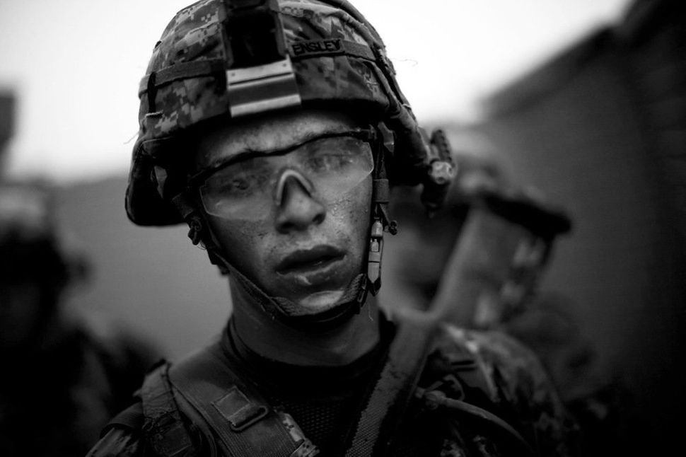Bravo Company's Pvt. Cody Lee Ensley walks through the safety of the gates at an American base after a daylong fierce attack