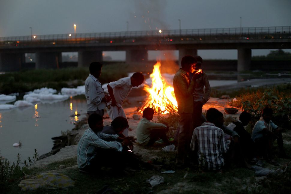 Men watch the fires of a cremation along the banks of the Yamuna River against the backdrop of the Wazirabad Barrage and floa