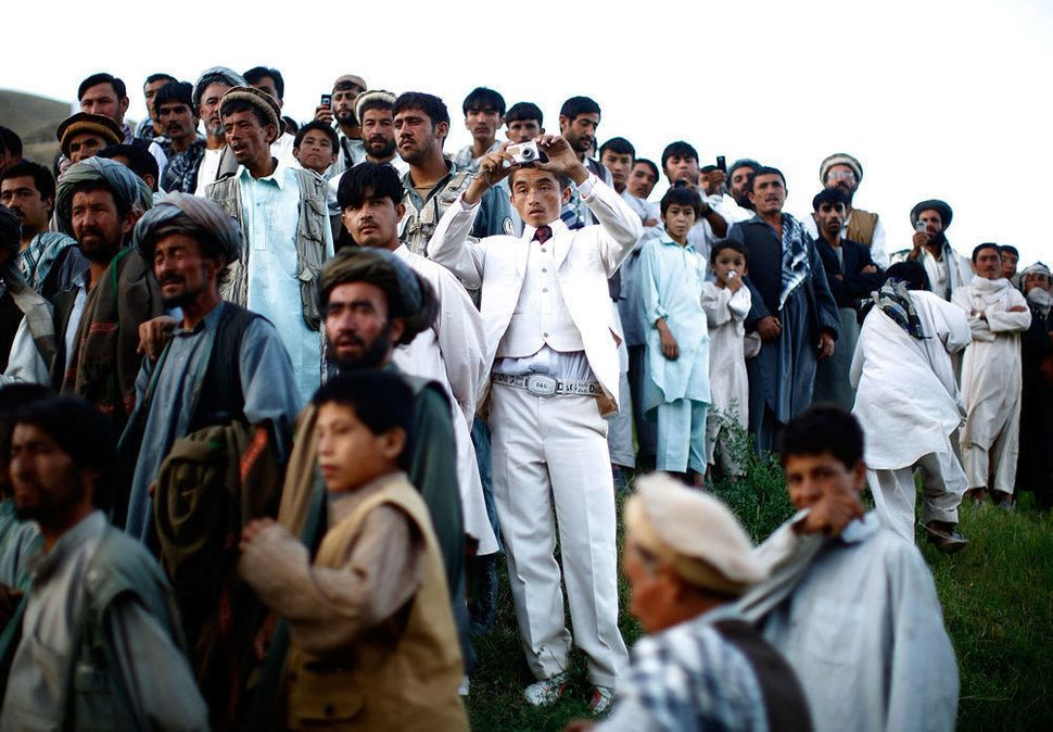 Afghan President Hamid Karzai held a rally in a remote village, where he struck a deal with an influential religious leader.