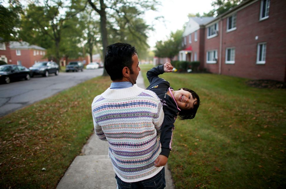 Omar Al-Awad holds his daughter as they walk home in Toledo, Ohio, where they were resettled after fleeing Syria and living i