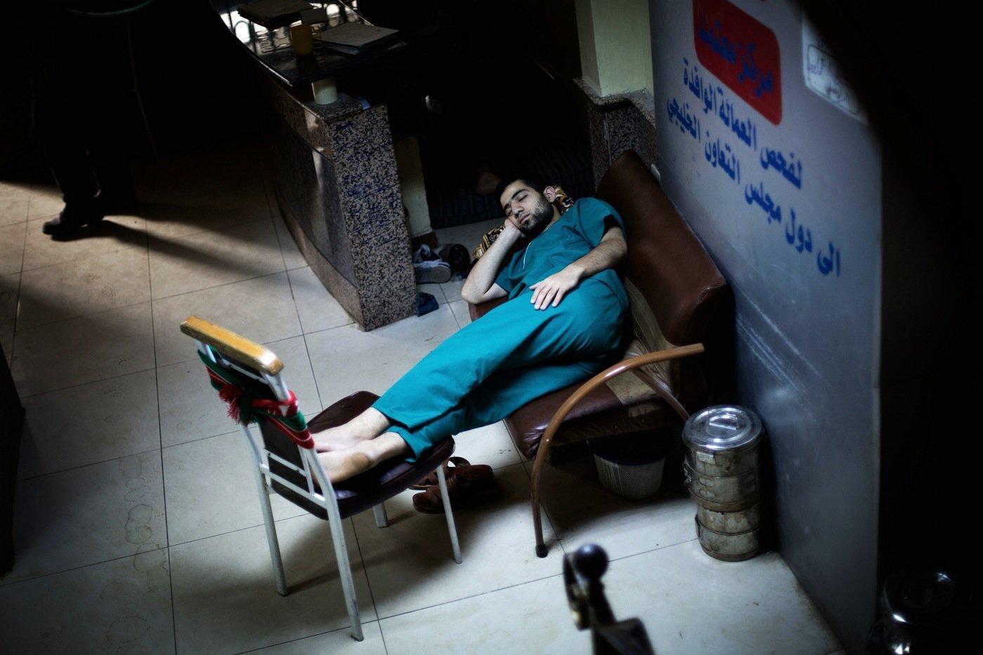 A Syrian doctor sleeps in the waiting room of Dar al-Shifa hospital in Aleppo on Oct. 21,