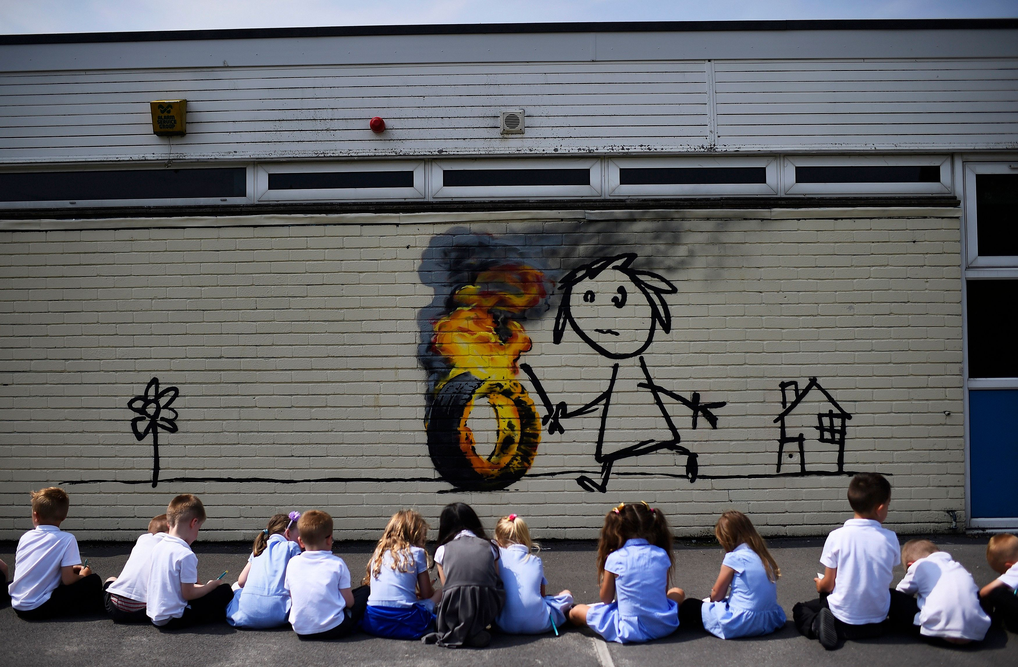 Reception class school children sit in a row as they draw a mural, attributed to graffiti artist Banksy, painted on the outside of a class room at the Bridge Farm Primary School in Bristol, Britain June 6, 2016.    REUTERS/Dylan Martinez