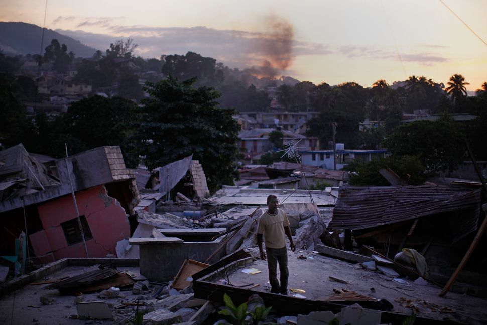 After Haiti's earthquake, a man stands on a rooftop yelling out for any sign of life from his missing relatives in a Port-au-
