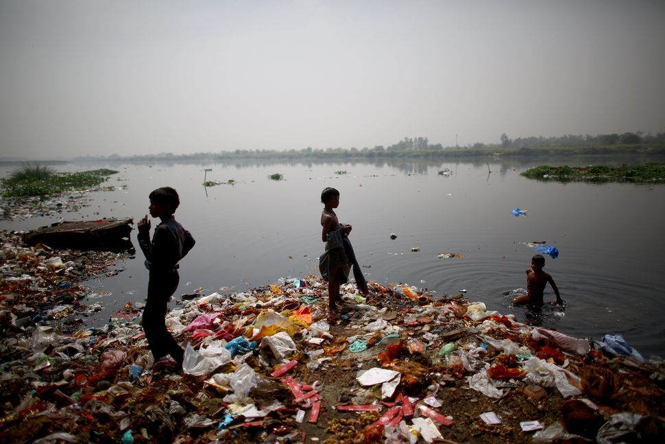 Children who live along the banks of India's Yamuna River in ramshackle huts hunt for coins and anything valuable they can co