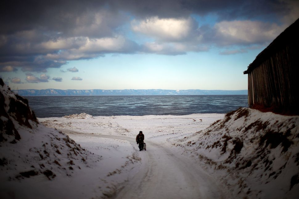 Storm clouds pass above a wintery landscape on the shores of Lake Baikal in central Russia. Baikal is the world's largest and