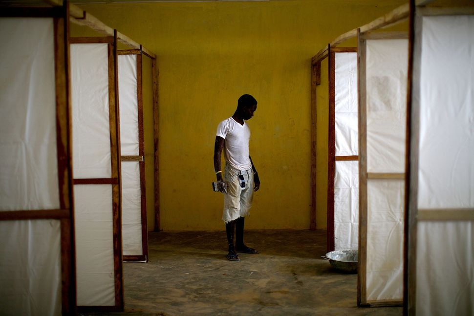 A worker stands by dividers to separate patients in an Ebola treatment facility under construction in the Port Loko district