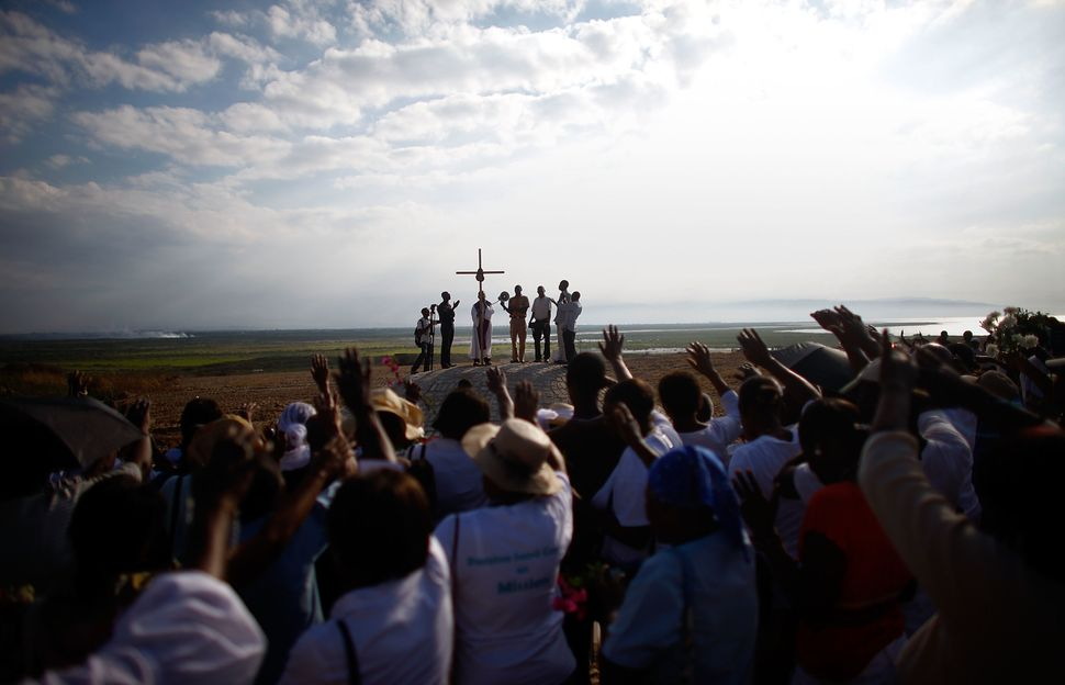 Parishioners from the Saint Louis King of France Catholic church in Port-au-Prince sing and cry as they dedicate a monument t
