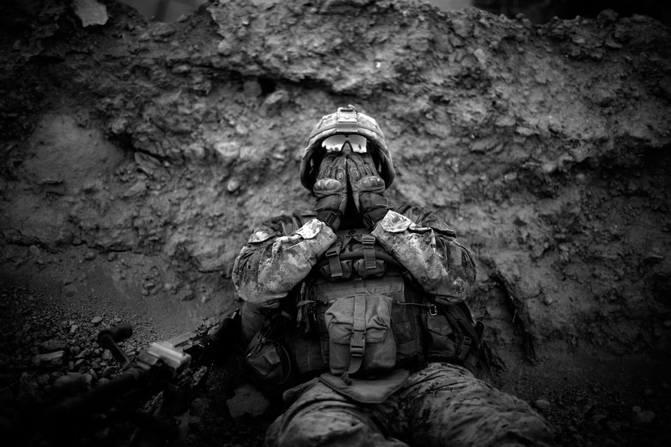 Marine Lance Cpl. Anthony Espinoza wipes the sweat out of his eyes at the end of a daylong patrol of the Sangin District in s