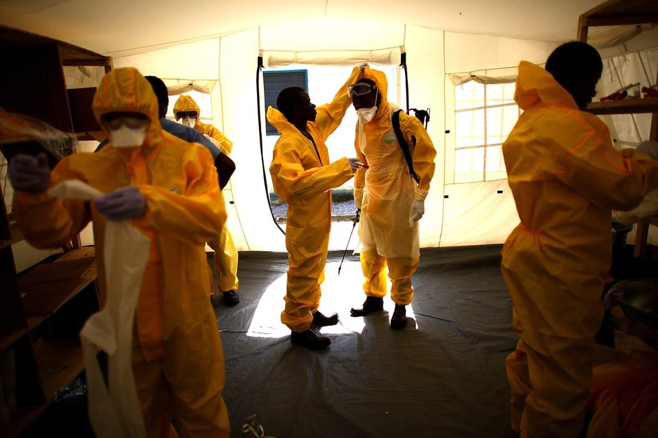 Volunteer workers at a Community Care Center for people suspected of having Ebola in northern Sierra Leone put on their