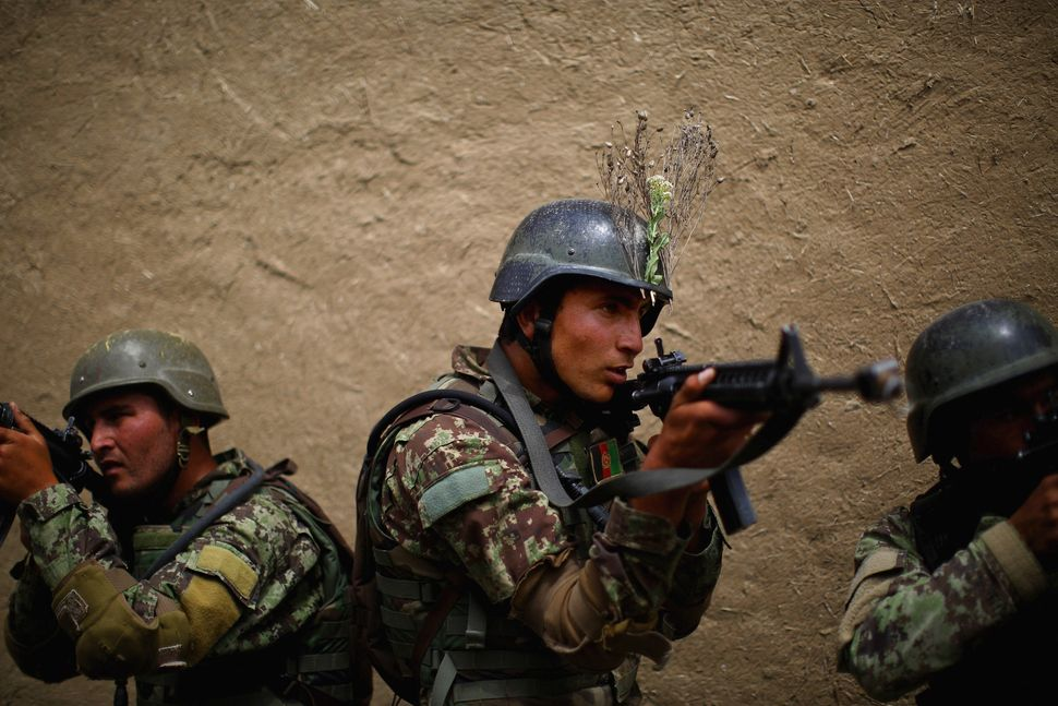 """Afghan commandos line up outside the walls of a mock compound before storming in to clear the area. """"My mission is to advise"""