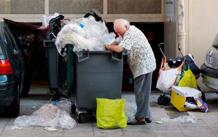 Eugene, an 87-year-old retired Frenchman, searches for food in a garbage container next to a supermarket in Nice June 13, 201