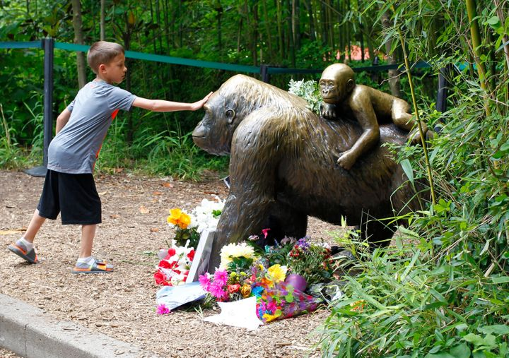 Visitors view a bronze statue of a gorilla and her baby surrounded by flowers outside the Cincinnati Zoo's Gorilla World exhi