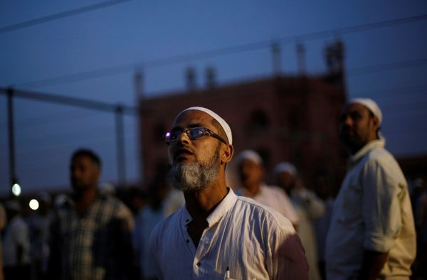 Muslim men look towards the sky to spot the crescent moon, on the eve of the holy fasting month of Ramadan, at the Jama Masji