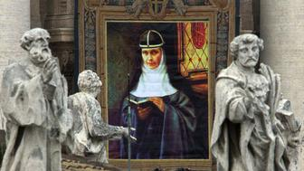 The portrait of Sweden's Maria Elisabeth Hesselblad (1870-1957), who gave refuge to Jews in her homeland during World War Two, is hung on St. Peter's facade behind other Saint's statues during her beatification ceremony in Vatican April 9. The Pope John Paul II set five people from Asia, Europe and Latin America who devoted their lives to helping the poor and sick on the road to sainthood.  VP/FMS