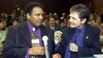 Boxing legend Muhammad Ali (L) and actor Michael J. Fox (R) talk before the start of a Senate subcommittee on Labor, Health, Human Services and Education hearing on Parkinson's Disease 22 May 2002 on Capitol Hill in Washington, DC. The celebrities who have Parkinson's asked the panel for more funds for Parkinson's research.      AFP POTO/Stephen JAFFE        (Photo credit should read STEPHEN JAFFE/AFP/Getty Images)