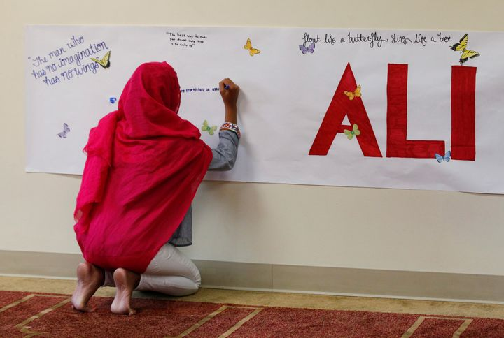 A member of the Louisville Islamic Center writes messages on a memorial banner as she pays her respect to Muhammad Ali, the f