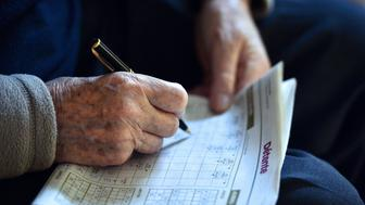 A pensioner fills in the crossword prior to Christmas eve dinner on December 24, 2014, at the St. Joseph retirement home in Nantes. AFP PHOTO/GEORGE GOBET        (Photo credit should read GEORGES GOBET/AFP/Getty Images)