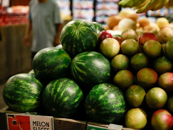 Bright green watermelons and blushing mangoesshare a table.