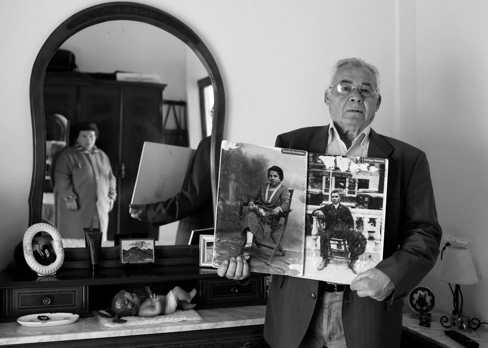 Antonio Narvaez Hernandez holds up photos of his parents Enrique Narvaez Borrego and Concepcion Hernandez Garcia, who both di