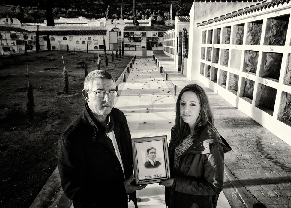 Cristobal Espinosa Guerrero stands with his daughter Maria in the cemetery of Teba, Malaga, next to a mass grave where the re