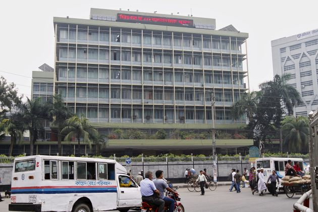 Commuters pass by the front of the Bangladesh central bank building in Dhaka March 8,