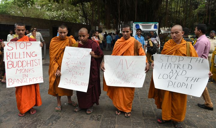 Indian Buddhist monks pose with placards during a silent protest in Mumbai on May 23, 2016, against the murder of an elderly