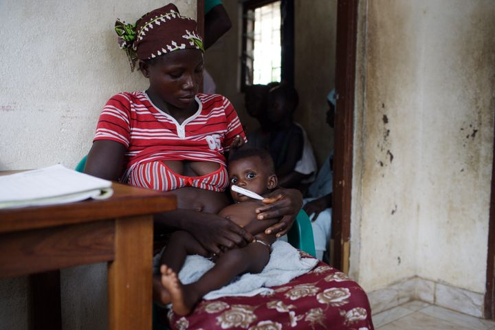 A woman and her children are seen waiting for HIV/AIDS volunteer testing and counseling in Binkolo, Sierra Leone.