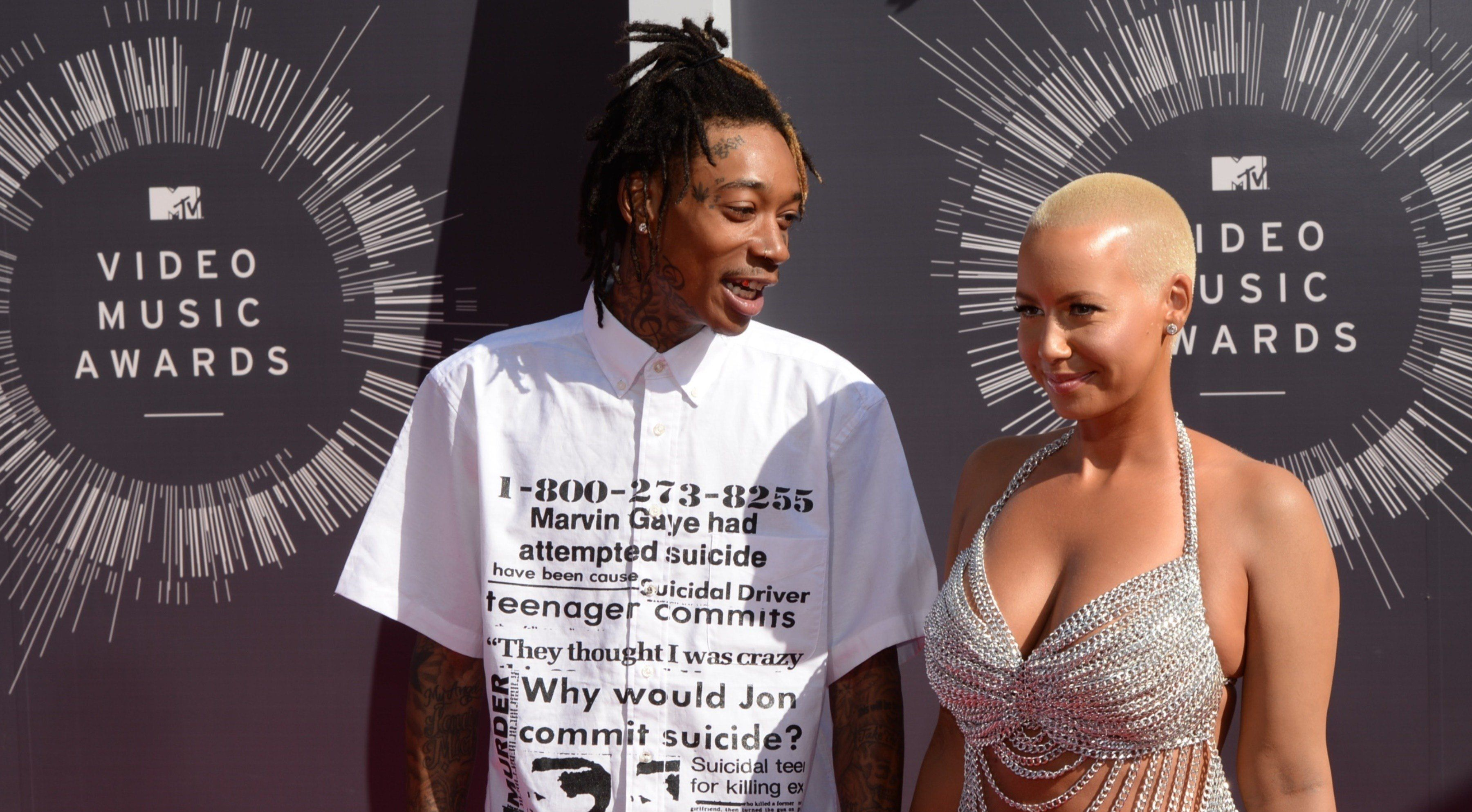Model Amber Rose (R) and rapper Wiz Khalifa (L) arrive on the red carpet at the MTV Video Music Awards (VMA), August 24, 2014 at The Forum in Inglewood, California.   AFP PHOTO / Mark Ralston        (Photo credit should read MARK RALSTON/AFP/Getty Images)