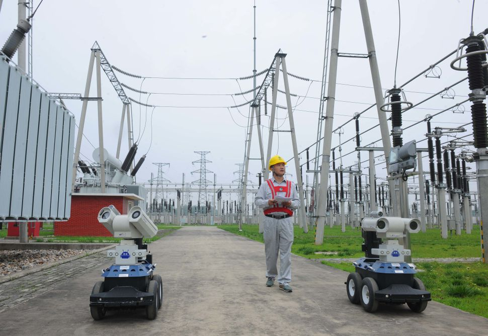 Aworker walks withtwo inspector robots at the station in Chuzhou. The robots can surveil the station's equipment
