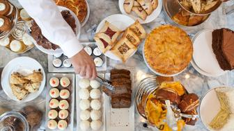 Person choosing pastries from tabletop selection