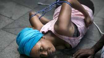 A migrant from Eritrea simulates what she says is a torture technique during a protest outside the European Union delegation in Israel, in Ramat Gan near Tel Aviv June 25, 2015. About 300 Eritrean migrants living in Israel held a protest on Thursday calling on the EU to act upon a U.N. inquiry report published earlier this month that showed human rights violations in Eritrea that may amount to crimes against humanity, including extrajudicial killings, widespread torture and enforced labour. REUTERS/Baz Ratner      TPX IMAGES OF THE DAY
