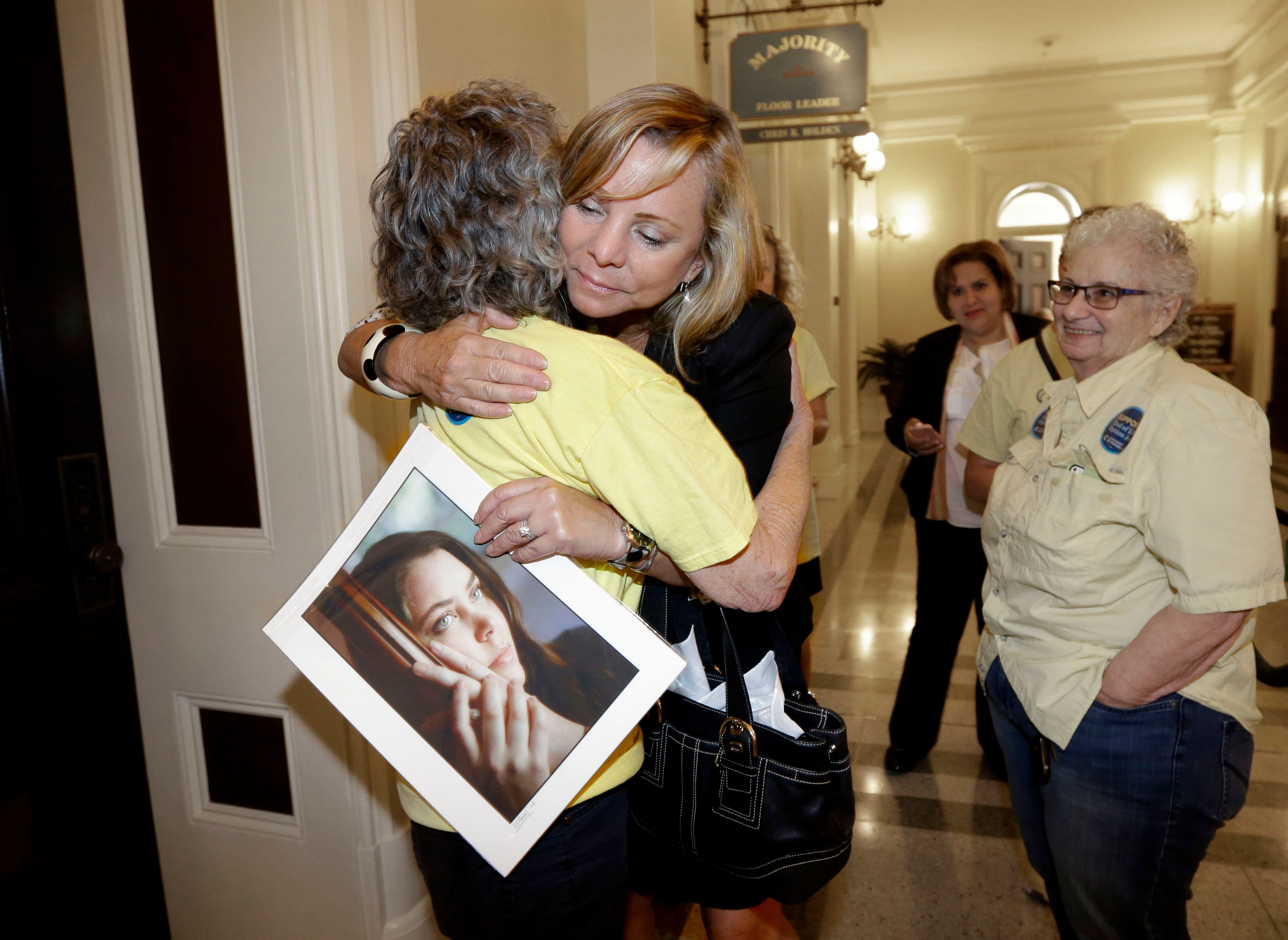Debbie Ziegler holds a photo of her daughter, Brittany Maynard, and get a hug after the California legislature appr