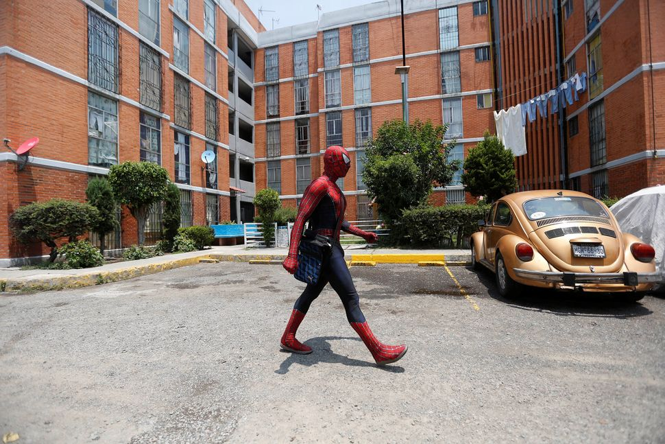 Walking outside the building where he lives, on his way to work in the Iztapalapa neighbourhood, in Mexico City, Mexico,&nbsp