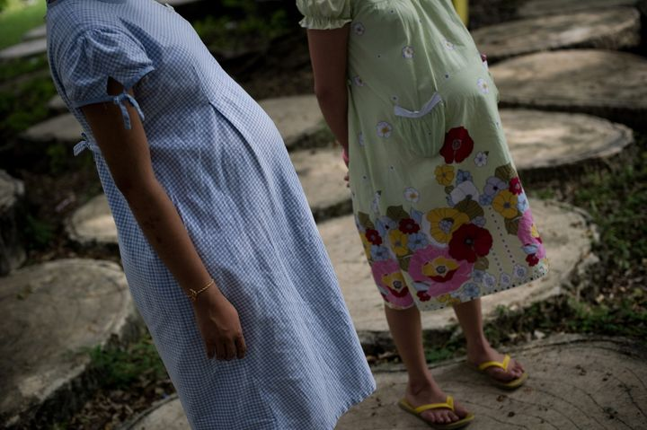 This picture taken on October 29, 2013 shows pregnant teenager Ying (L), 16, standing with another pregnant woman (R) at the