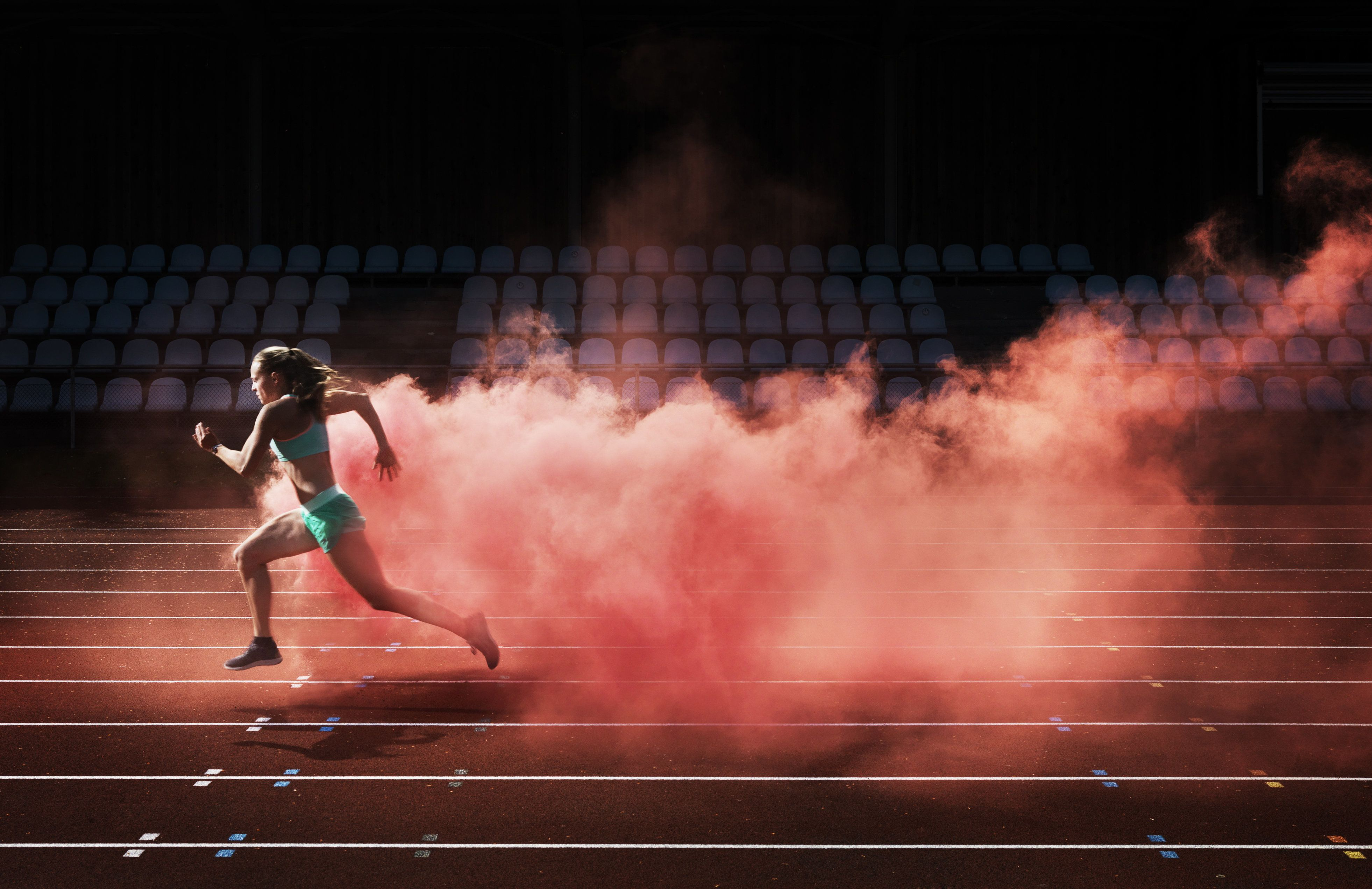 female athlete running in red smoke on stadium