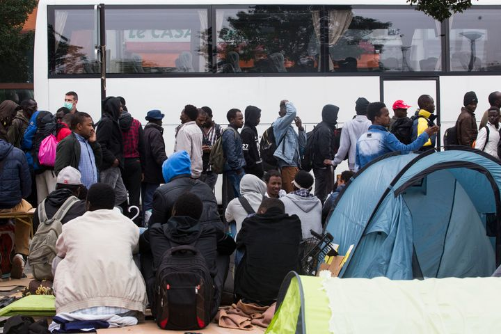 Migrants stand in line next to a bus during the evacuation of the migrants camp at Jardin d'Eole, in Paris on June 6, 2016.