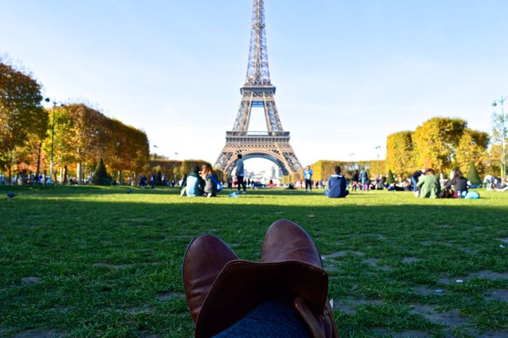 Having a picnic and drinking wine in front of the Eiffel Tower