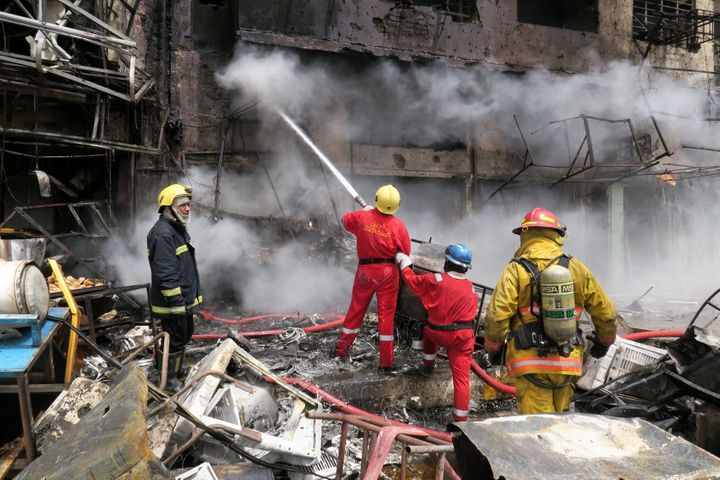 Firemen hose down a burning building at the site of car bomb attack in Baghdad al-Jadeeda, an eastern district of the Iraqi capital.