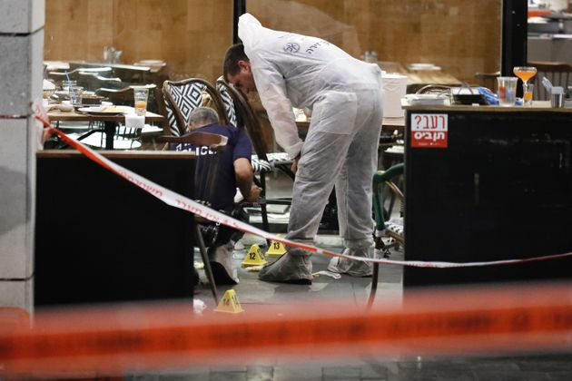 Israeli forensic police inspect a restaurant following the shooting attack at a shopping