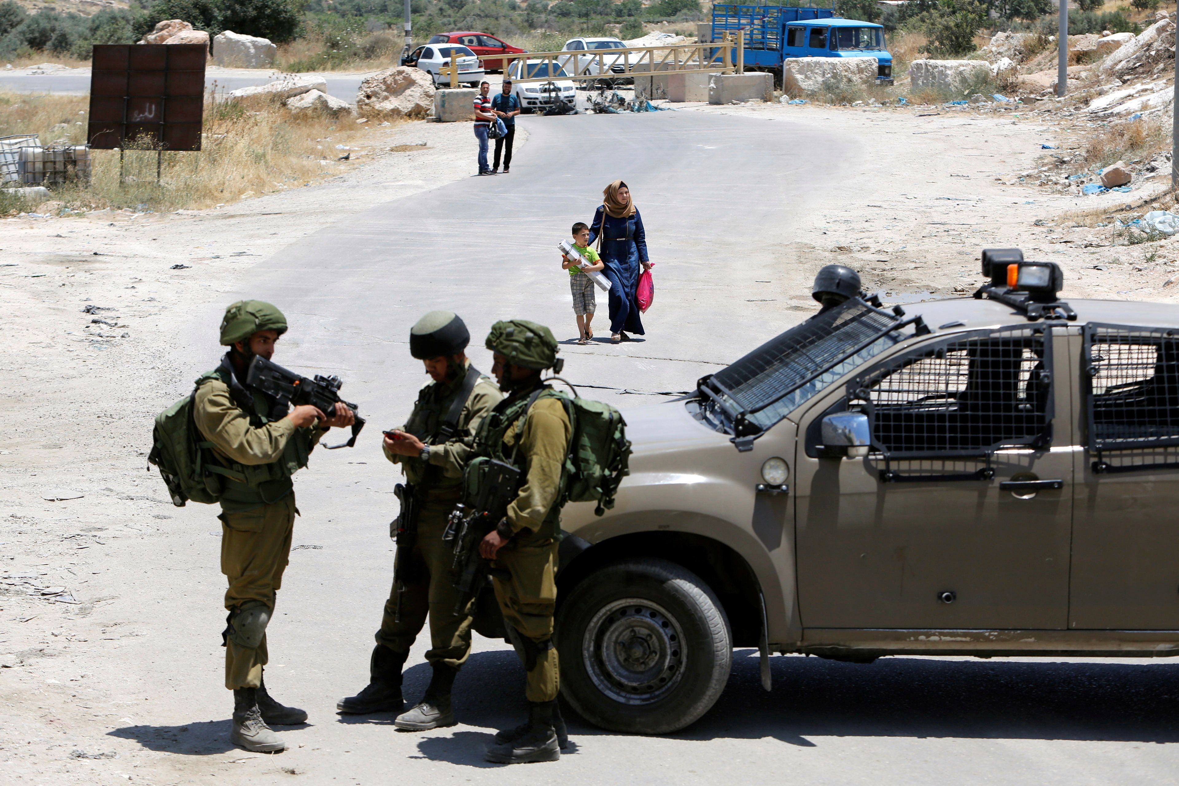 Israeli soldiers stand guard at the entrance of Yatta near the West Bank city of