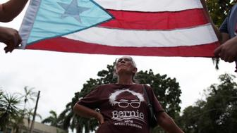A supporter of U.S. Democratic presidential candidate Bernie Sanders stands behind a Puerto Rican flag in San Juan, Puerto Rico, May 16, 2016. REUTERS/Alvin Baez