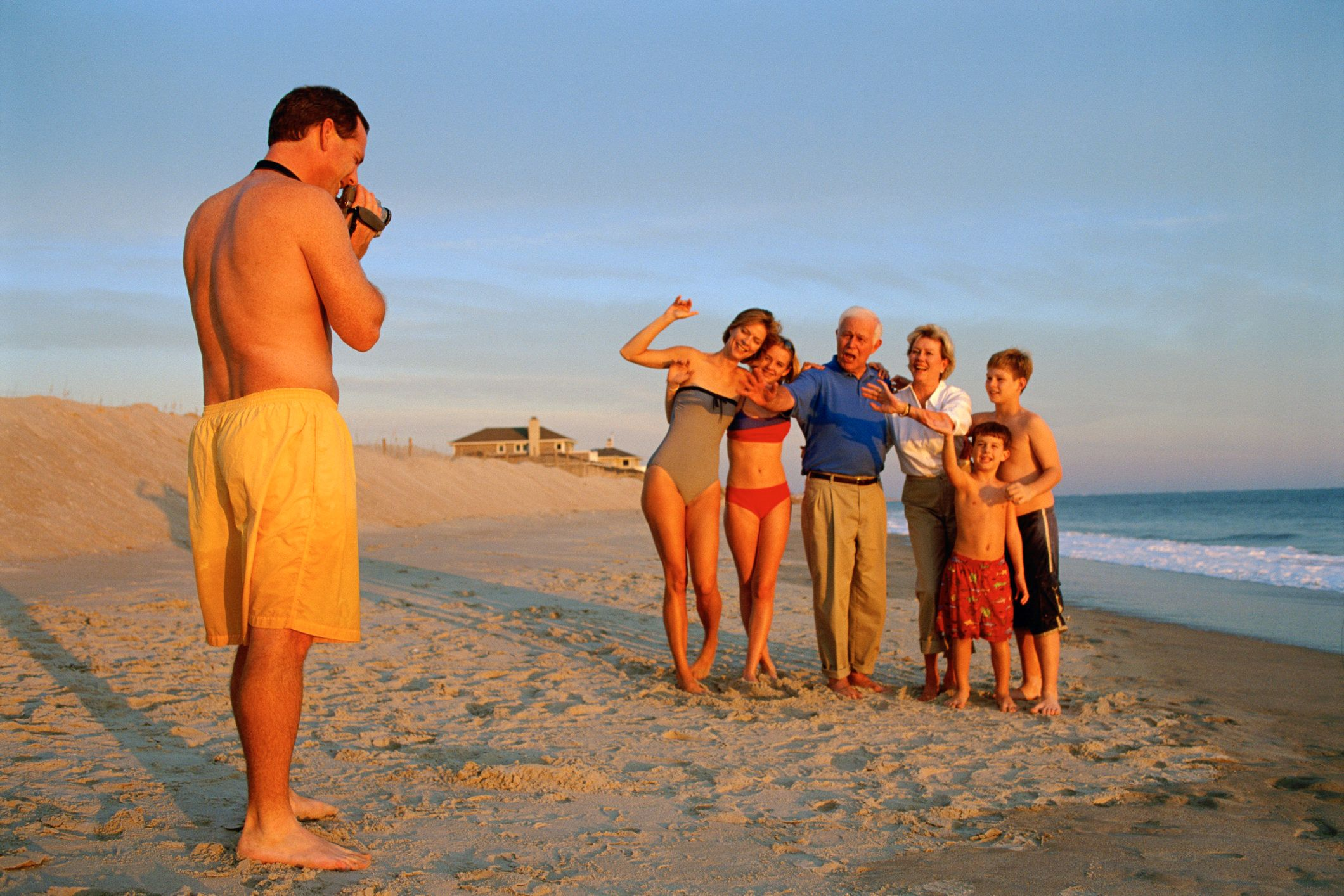 Man videotaping family on beach