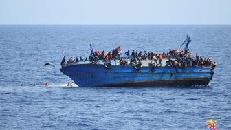 "Migrants are seen on a capsizing boat before a rescue operation by Italian navy ships ""Bettica"" and ""Bergamini"" (unseen) off the coast of Libya in this handout picture released by the Italian Marina Militare on May 25, 2016. Marina Militare/Handout via REUTERS    ATTENTION EDITORS - THIS PICTURE WAS PROVIDED BY A THIRD PARTY. FOR EDITORIAL USE ONLY.       TPX IMAGES OF THE DAY"
